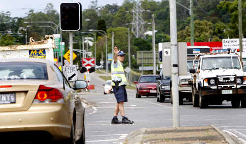Police control traffic along Brisbane Road where traffic lights were not working due to power outages.