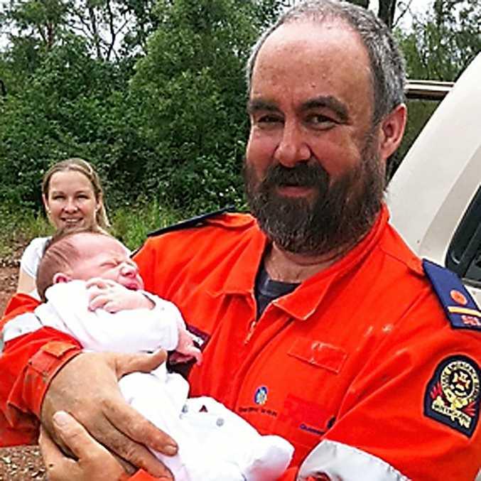 Jade Nixon watches as Crows Nest SES volunteer Paul Kerans nurses her 12-day-old son Thomas.