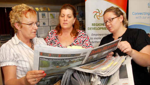 Christine Stevens, left, and Kym Spandley check out the flood coverage in the Daily Mercury with conservation volunteer Caitlin Davies at Mackay Regional Social Development Centre.