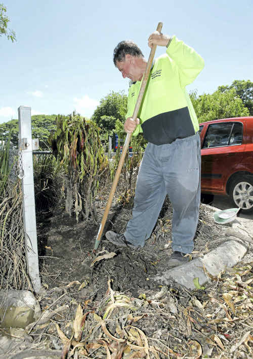 Neil Fisher removes mulch from a garden bed at Central Queensland Christian College to help the ground to dry out.