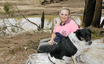Charlotte Bull and her dog Captain survey the damage the floodwaters wrought.