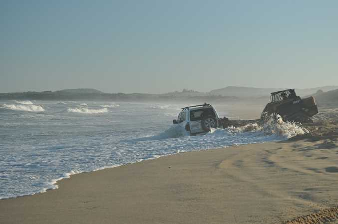 The unlucky owners of this 4WD watched as the tide lapped against the stranded vehicle. Large seas and high tides have softened local beaches.