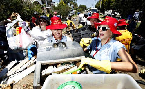 Maroochy Surf Club members Ines Kharoumi, Erica Ricketts and Julia O'Brien (l-r) help the army to clean up Roy Street in North Booval after flood waters inundated many of the properties in the Ipswich suburb.