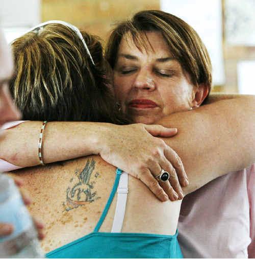 Premier Anna Bligh comforts flood victim Liz Robinson at the Showgrounds evacuation centre.