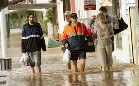 LOCALS wade through water as it crept into shops on the main street. PHOTO: LUKE WILLEY.
