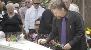 John Tyson places a rose on the coffins of his partner, Donna Rice, and son, Jordan at their funeral in 2011