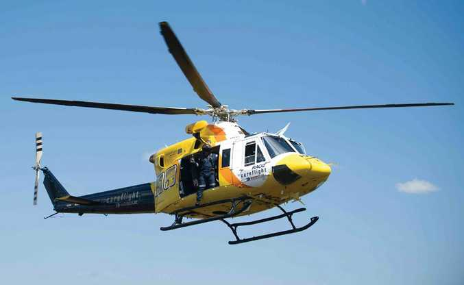 An RACQ CareFlight helicopter performs a rescue during the recent flood disaster.