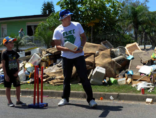 ON FIRE: Ipswich product and Australian test cricketer Shane Watson plays a game of cricket among the debris with children on David Street at North Booval, Ipswich. Photo: Dean Lewins-AAP