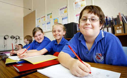 Brassall Primary School students from left, Kirra Johns, nine, Talia McIntosh, nine, and Luke Koimans, nine, were back in class again yesterday.