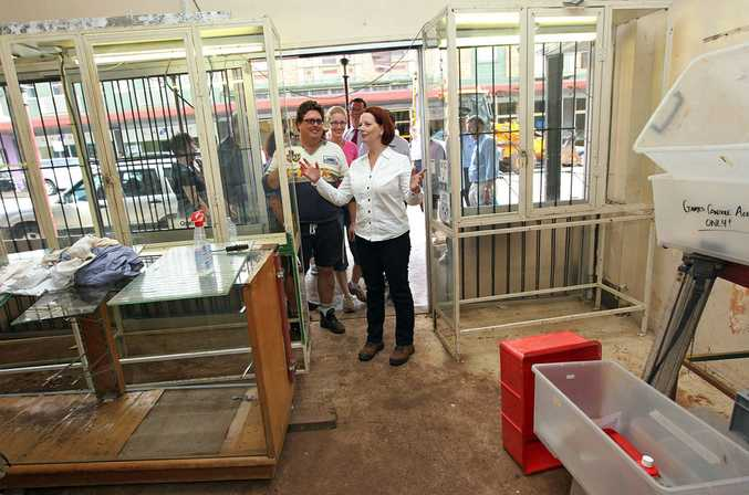 Prime Minister Julia Gillard visits a flood-affected business in Russell Street on January 14.