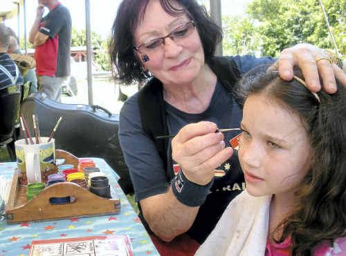 Priscilla Barrett paints the face of young Danielle Aguis.