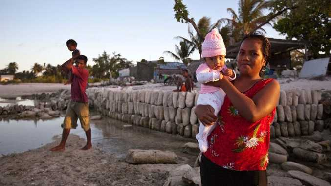 Era Tatabo with Daughter Tawana (4 months), standing at the former site of her home that was washed away.