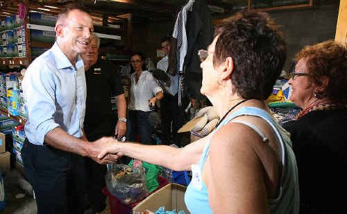 Opposition leader Tony Abbott meets volunteer workers in the Gatton relief distribution centre in Railway Street Gatton on Friday.