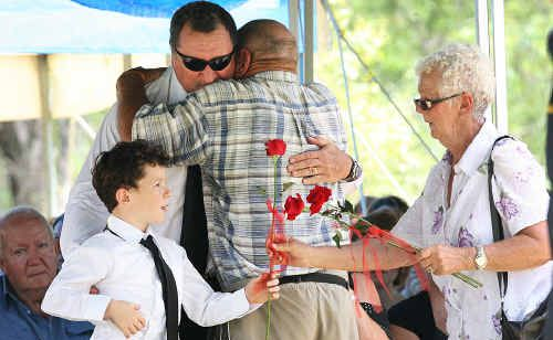Zachary Jibson and father Danny McGuire (at rear in dark glasses) at yesterday's heart wrenching funeral of Llync-Chiann Clarke, Jocelyn Jibson and Garry Jibson in Gatton yesterday. Zachary placed three roses on the coffins of his three lost family members.