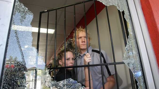 Derek Hicks and Emma Bowhay inspect the damage of their computer shop at Bowman Street, Caloundra after it was broken into.