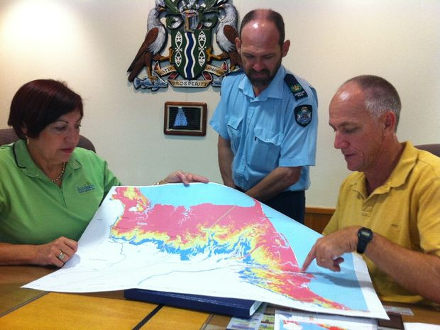 Burdekin Shire Mayor Lyn McLaughlin, Ayr Police officer-in-charge senior sergeant Steve Barton and council operations manager Trevor Williams consult the storm surge map for the region at the Local Disaster Management Group meeting this morning.