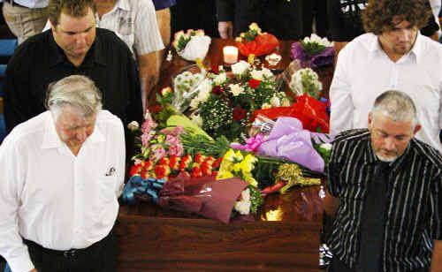 Friends and family surround the casket of Bruce Allan Marshall during his funeral service.