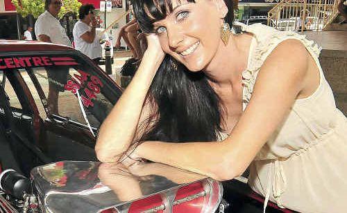 Promotional model 'Lizard' shows off Jody Jackson's supercharged LX Torana Hatchback in the Bundaberg CBD.