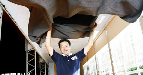 Andy Huang, volunteer for the Tzu Chi Foundation, with one of the blankets the buddhist group is donating to flood victims.