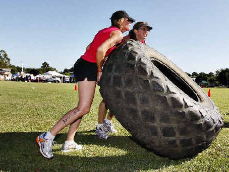 Lisa McLaughlin (left) and Janine Davey tackle the tyre flip challenge at the Lismore Samson Fitness Challenge at Mortimer Oval in Lismore yesterday.