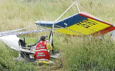 QFRS incident controller Peter Mackenzie inspects a Drifter ultralight aircraft after a 27-year-old student pilot crashed near the Clifton Airfield yesterday.