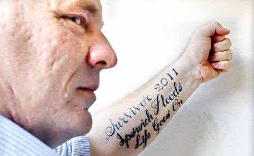 Blackstone resident Gavin Berry with his recent tattoo to mark the 2011 Ipswich floods.