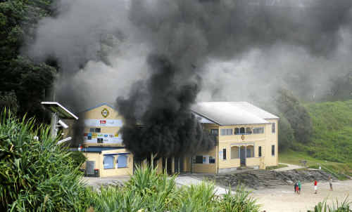The boatshed at the Yamba Surf Club spews smoke over Main Beach and the Pacific Hotel.
