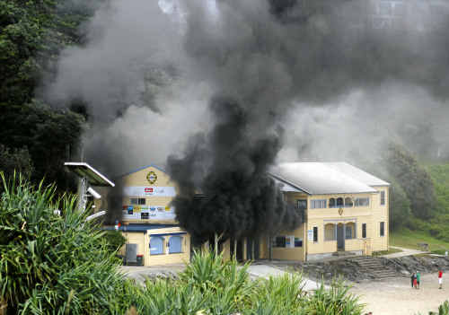 Smoke pours from the boatshed at the Yamba Surf Club during yesterday's dramatic blaze.
