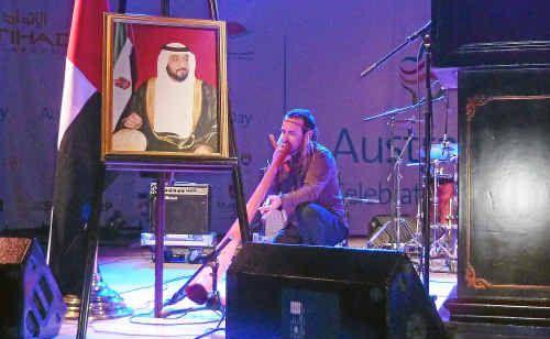 Coffs Coast didgeridoo player Kristian Benton performs under a portrait of Sheikh Zayed the ruler of Abu Dhabi.