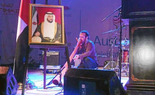 Coffs Coast didgeridoo player Kristian Benton performs under a portrait of Sheikh Zayed the ruler of Abu Dhabi.