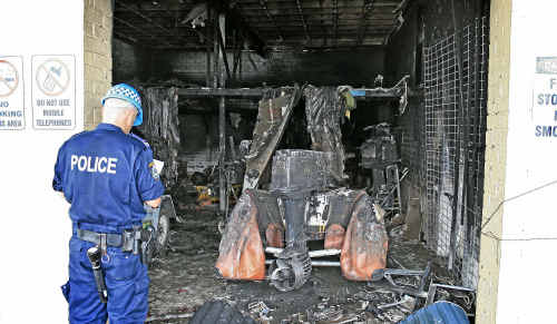 A forensic services officer surveys the damage from Tuesday's fire at the Yamba Surf Club.