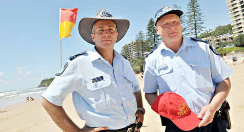 Senior Sergeants Stephen McReight and Hardy Wirth juggle their police and surf lifesaving hats.