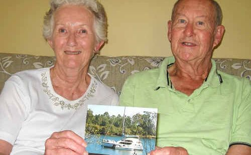Anne and Noel Buzaglo with a photo of their catamaran, Perwinji.