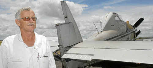 A relieved Rob Thomson, 60, stands beside his plane which had the rudder and tail fin ripped off after clipping low-lying power lines.