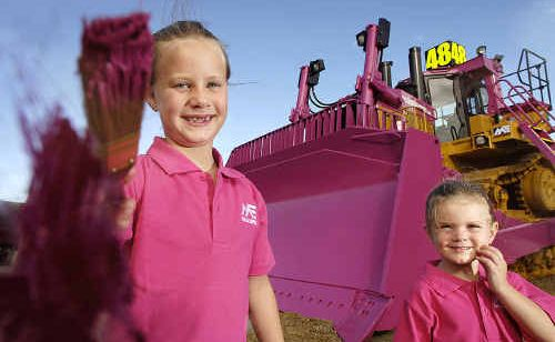 Lucy (left) and Maggie Jauncey are pretty pleased their dad was happy to paint a bulldozer pink for them.