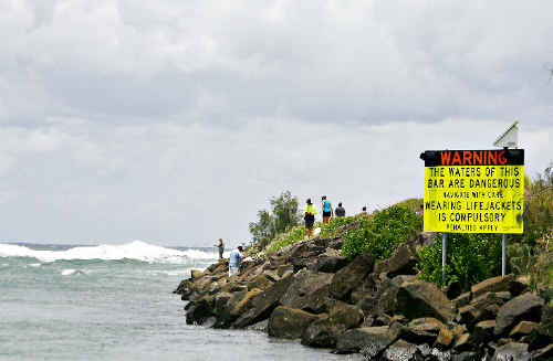 A sign on the rockwall at the entrance to the Brunswick Heads bar warns boat owners of possible dangerous conditions ahead.