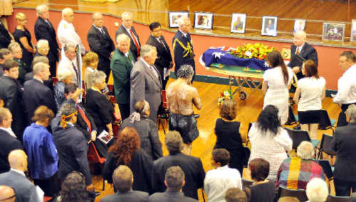 The scene inside the Armidale Town Hall yesterday when 400 people gathered for the State funeral of former Lismore boxer Frank Roberts. Hundreds of others sat or stood outside in the street. The stage area had a backdrop of the Aboriginal flag and a large projected image of Roberts, while family photographs were arrayed along the front. The casket was draped in the Australian and Olympic flags and the boxing belt awarded to Roberts for his achievements in the sport.