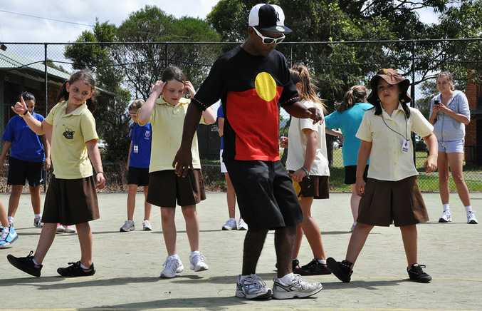Break dancer Jason Campbell goes through some moves with kids at the Wyong Vibe 3on3.