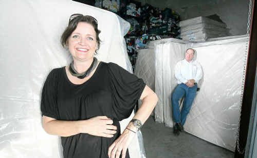 Kick Furniture's Lisa Kinross delivers mattresses to Lifeline Ipswich and West Moreton business manager Colin Hannigan for flood-affected families.