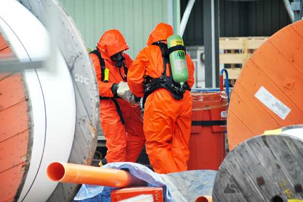 Hazardous materials personnel get to work at the Country Energy Field Service Station where a forklift punctured bags of sulphur.