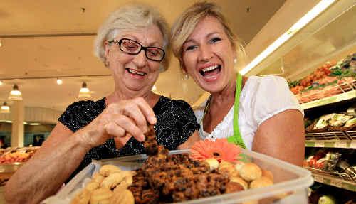 Kim McCosker gives Laurel Hanna a piece of her ginger fruit cake to try.