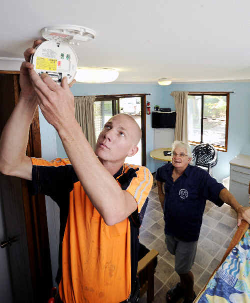 Suffolk Beachfront Holiday Park manager Paul Brooks watches as Elliot Dewhurst, from North East Electrical, performs a routine check on smoke alarms installed in one of their cabins.