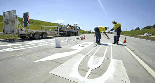 Aaron Lancaster, left, and Milton Berghan, from Allstate Linemarking, put the finishing touches to the speed markings on the road surface of the northern section of the Ballina bypass.