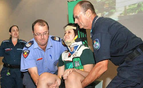 Year 12 student Krista Skinner is put in a brace by Chris Cahill, left and Carl Christensen.