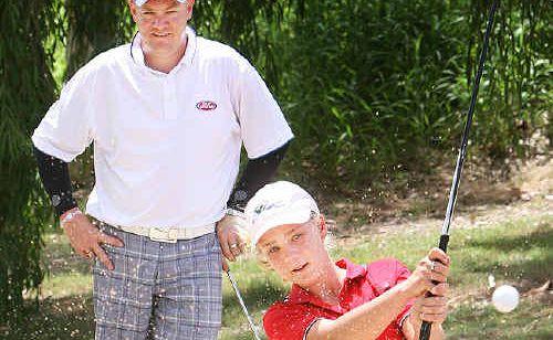 Trainee golf professional Nev Austin checks the progress of promising Sandy Gallop player Tahlia Condon.