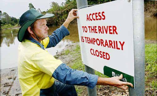 Ipswich City Council worker Ross Murphy puts up a river closure sign.