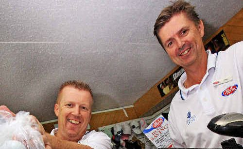 Tweed Heads-Coolangatta Golf Club Pro Shop staff, brothers Garry and Russ Davis, preparing for the charity golf event.