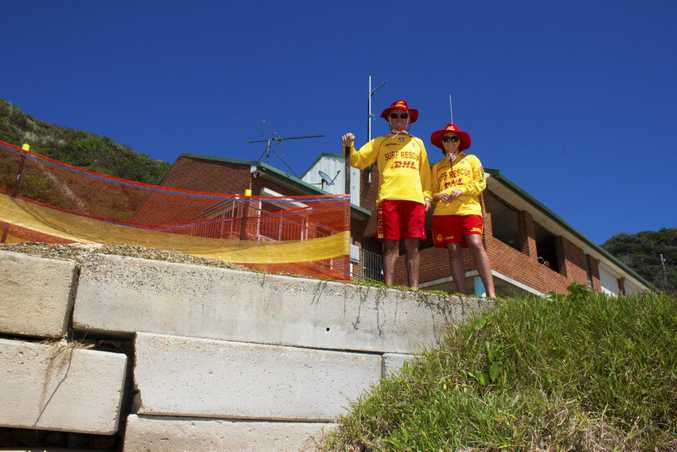 Nambucca Heads surf lifesavers Greg and Hannah Iredale stand near the failing retaining wall.