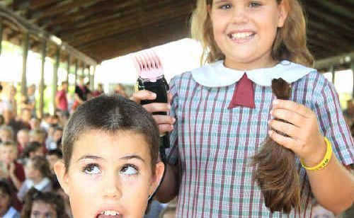 Twin sisters Jassmin (seated) and Lucie Jones-Calvert shave their heads for charity at St James Primary School, Banora Point.