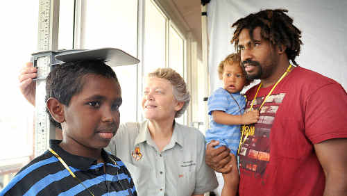 Benny Repu, 10, gets a health check from Suzanne Lee as dad Benny and brother Daniel, 1, look on.